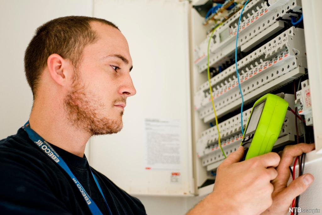 Elektriker utfører målinger i sikringsskap. Foto.
