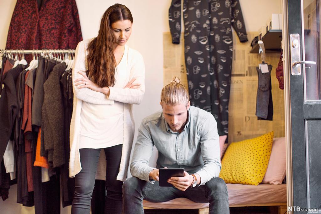Ung mann sitter med nettbrett i klesbutikk. Ung kvinne med armene i kors står ved siden av. Foto.
