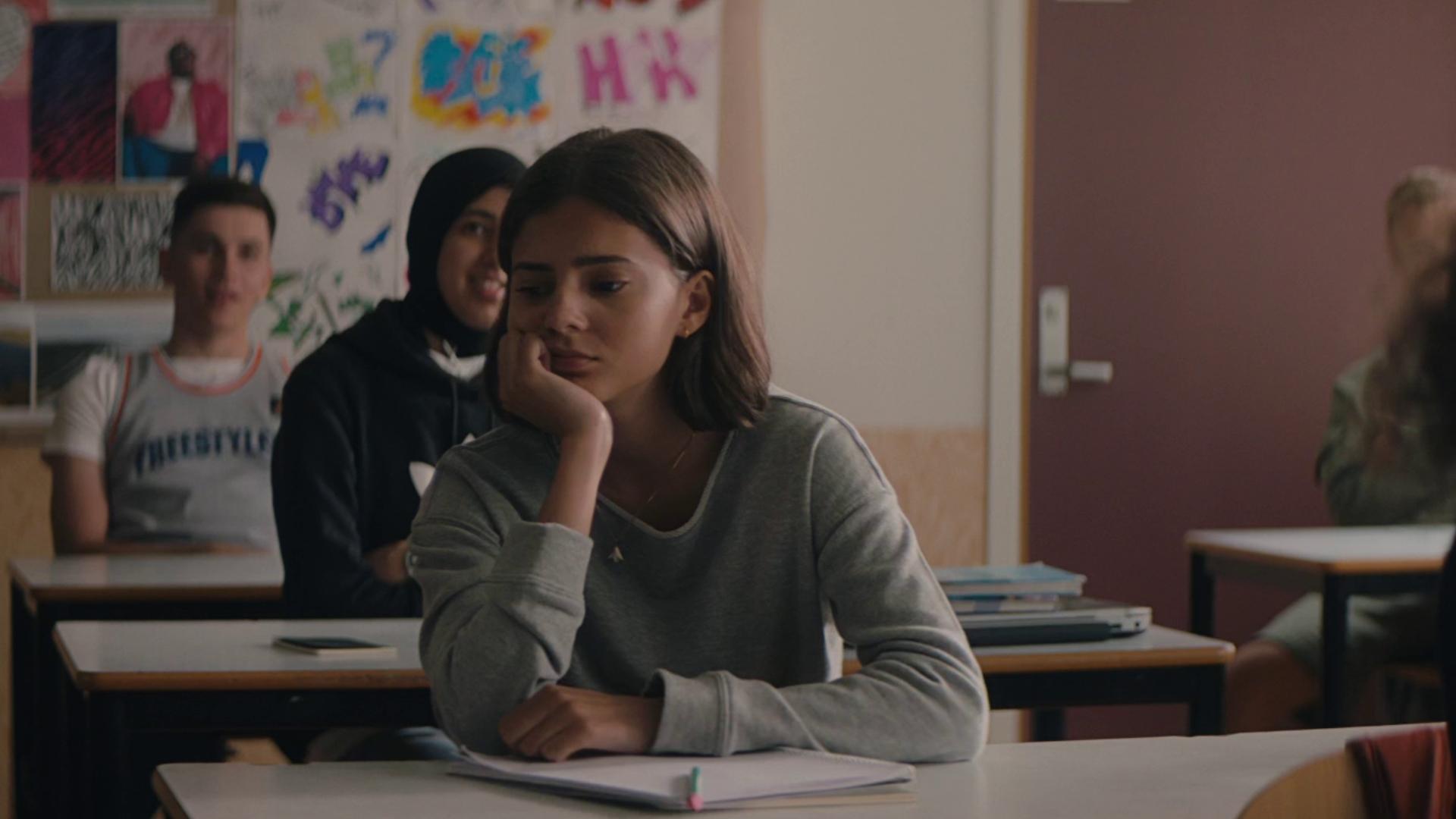 Jente sitter ved skolepult. Foto.
