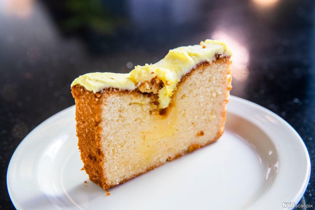 Et firkantet stykke sitronkake med glasur på en hvit asjett. Foto.