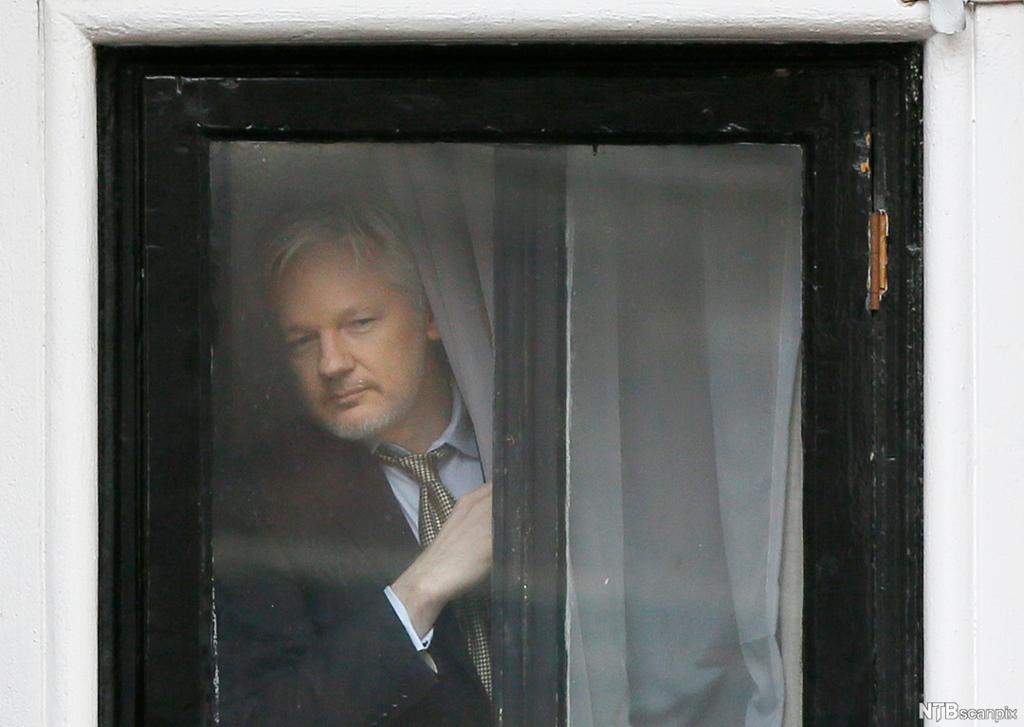 Mann titter ut av vindu. Foto.