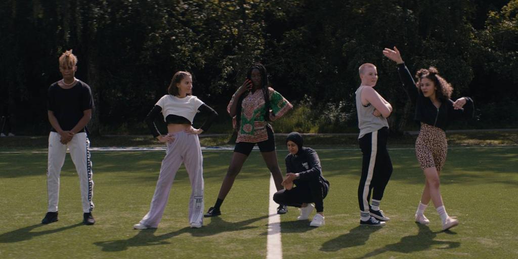 """Scene fra filmen """"Alle utlendinger har lukka gardiner"""" der seks av ungdommene framfører en dans på fotballbanen. Foto."""