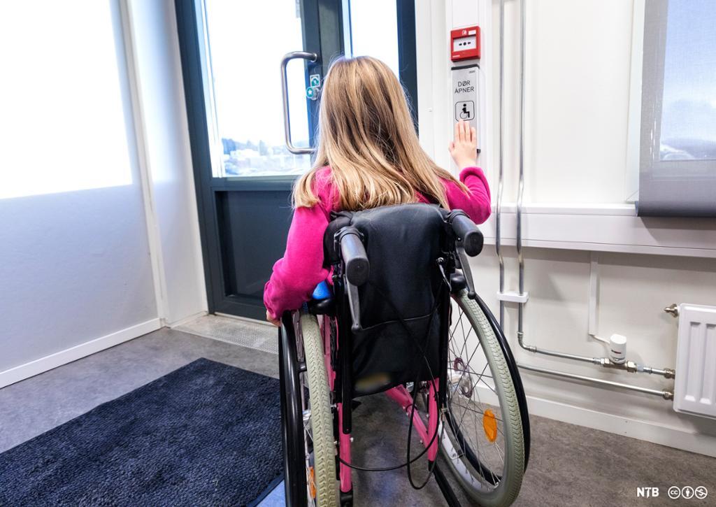 Ung jente i rullestol trykker på døråpnerknapp. Foto.