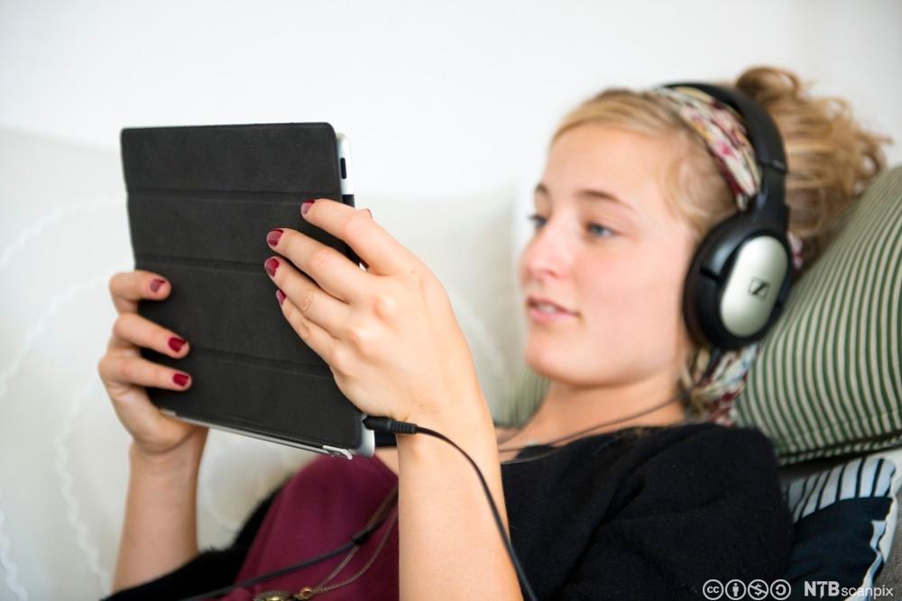 Jente ser film på nettbrett. Foto.