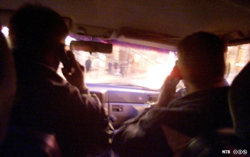 To personar, sett bakfrå, sit i ein bil mens dei kommuniserer og overvaker bylivet, som vi ser gjennom frontruta. Foto.