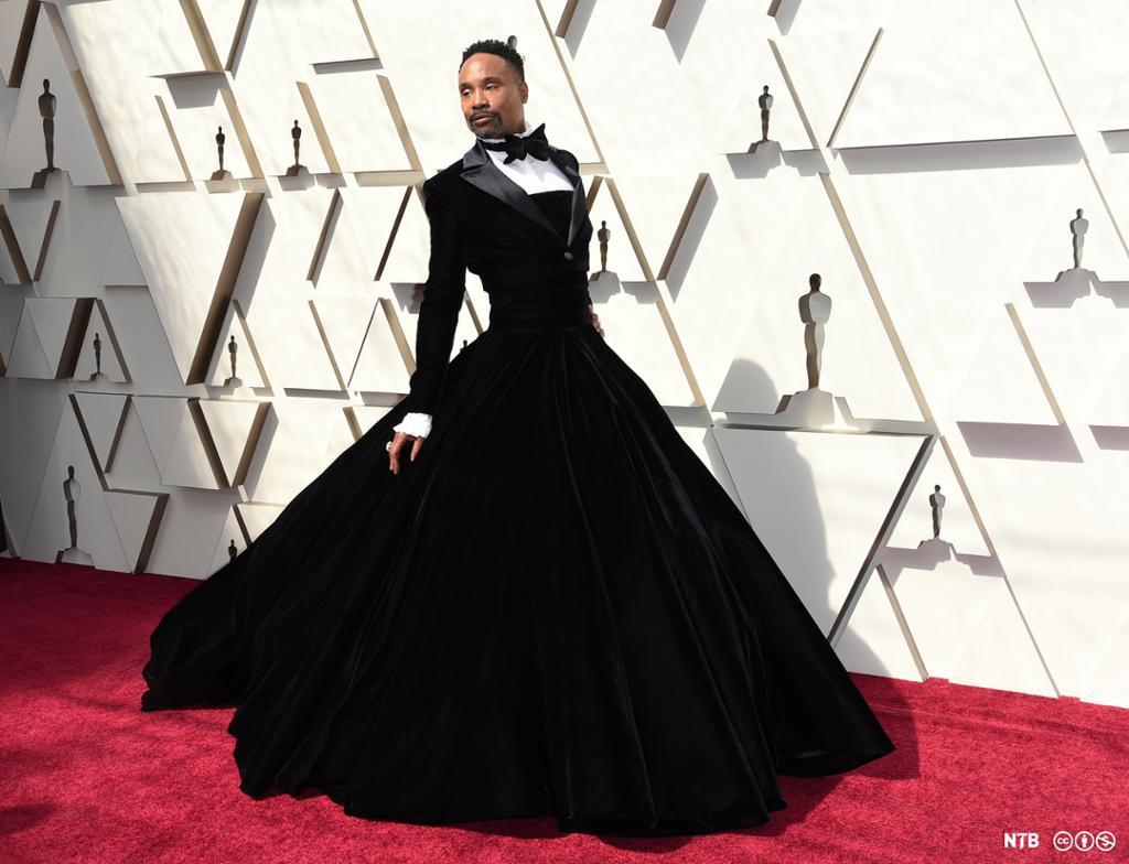 Skodespelaren Billy Porter i svart kjole med smoking-overdel på raud laupar. Foto.