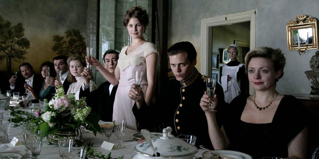 Utsnitt fra filmen Victoria. Pent kledde personer sitter ved et pent dekket langbord og løfter glasset. En ung kvinne ved midten av bordet står oppreist, og de andre sitter. Foto.