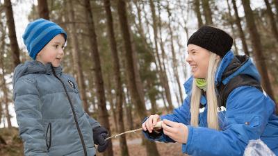 Liten gutt får hjelp av en voksen til å tvinne pinnebrød på en pinne. Foto.