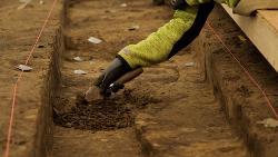 En person graver forsiktig i jorda med et lite verktøy som arkeologer bruker. Vedkommende ligger på magen, og vi ser bare hånden. Foto.