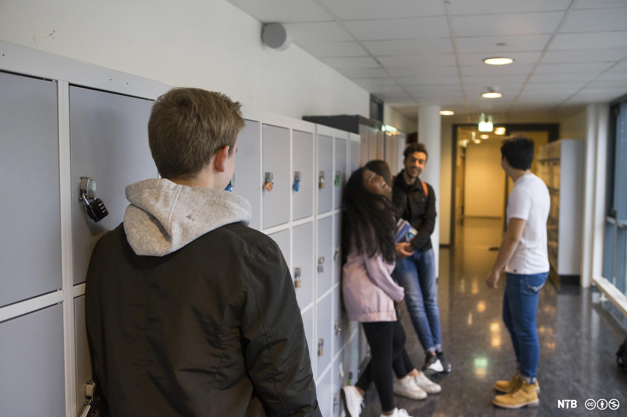Ein elev lener seg mot eit bokskap og ser bort på fire andre ungdommar som står litt lenger borte og snakkar og ler. Foto.