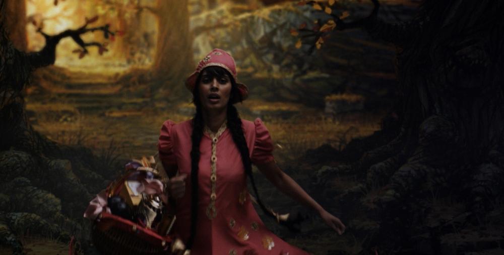 Jente i rosa kjole løper gjennom en mørk skog. Foto.