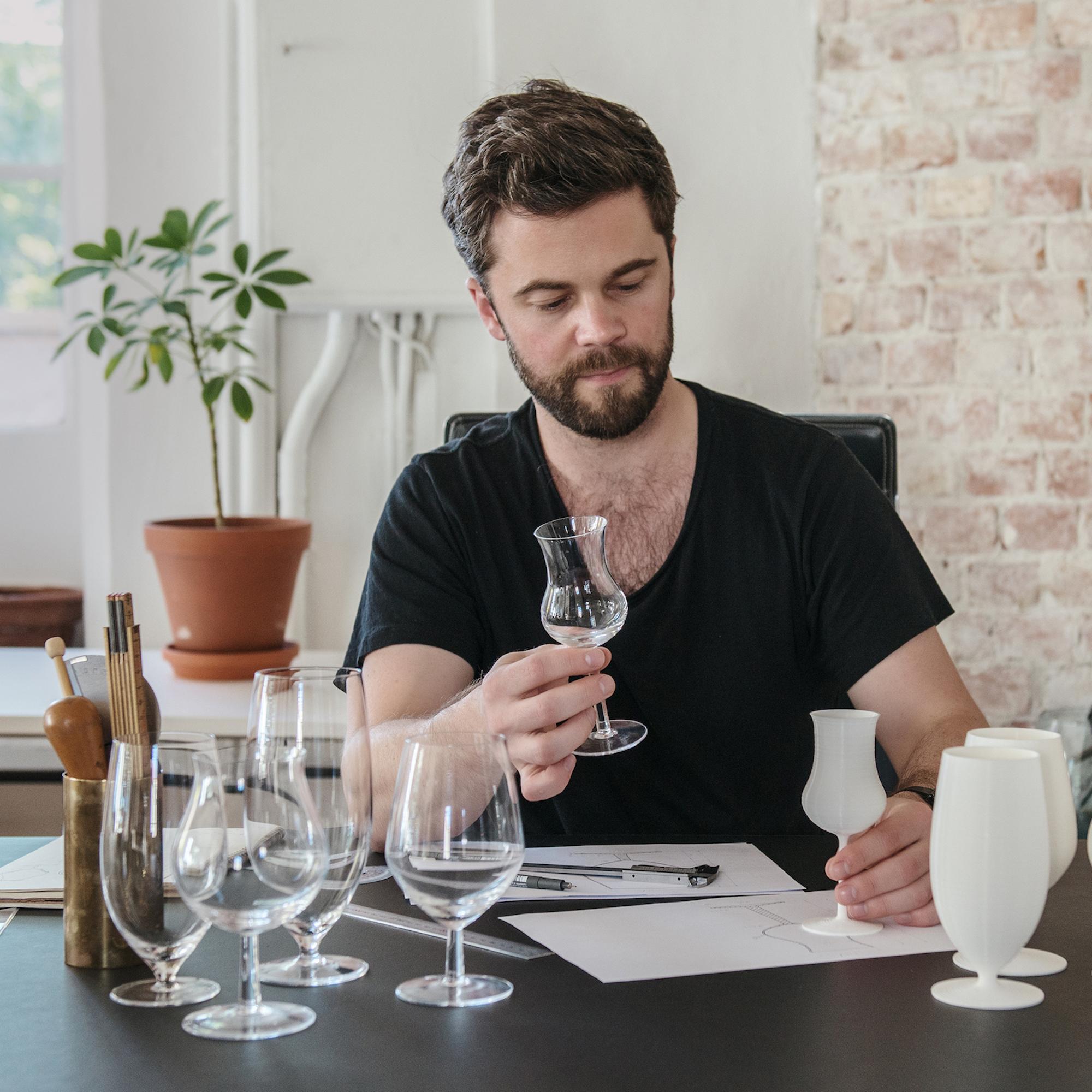 Mann sitter ved et bord og betrakter glass i ulike former. Foto.