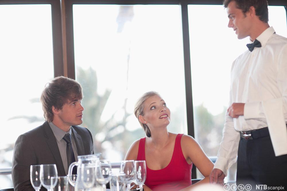 En servitør snakker med to gjester i restauranten. Foto.