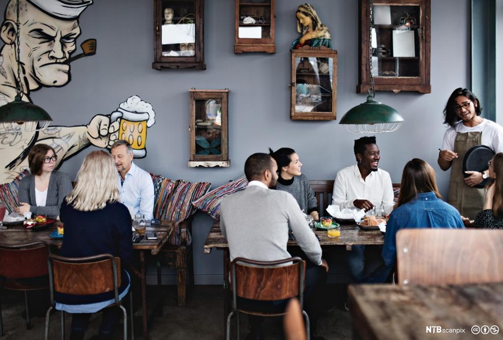 Servitør snakker med gjestene ved et av bordene i en kafe. Foto.