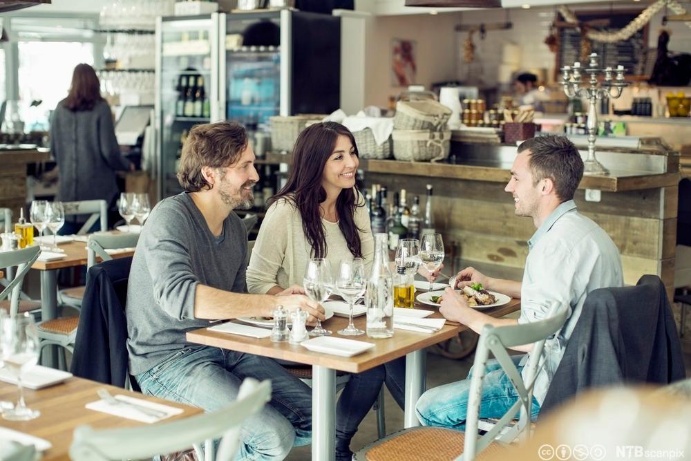 Tre gjester som spiser middag på en restaurant. Foto.