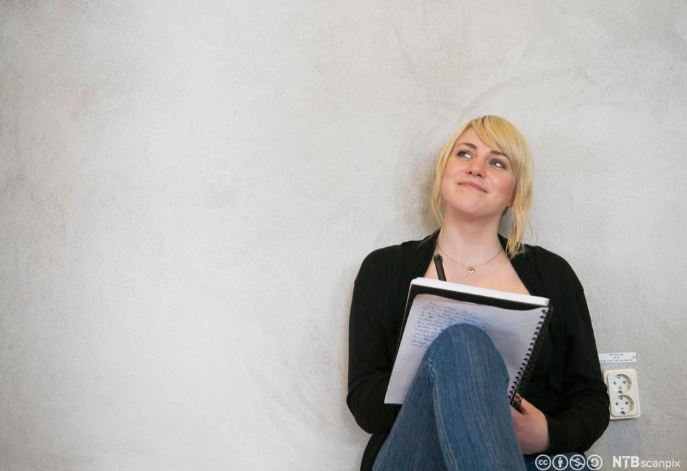 Jente sit med skriveblokk på knea og smiler. Foto.