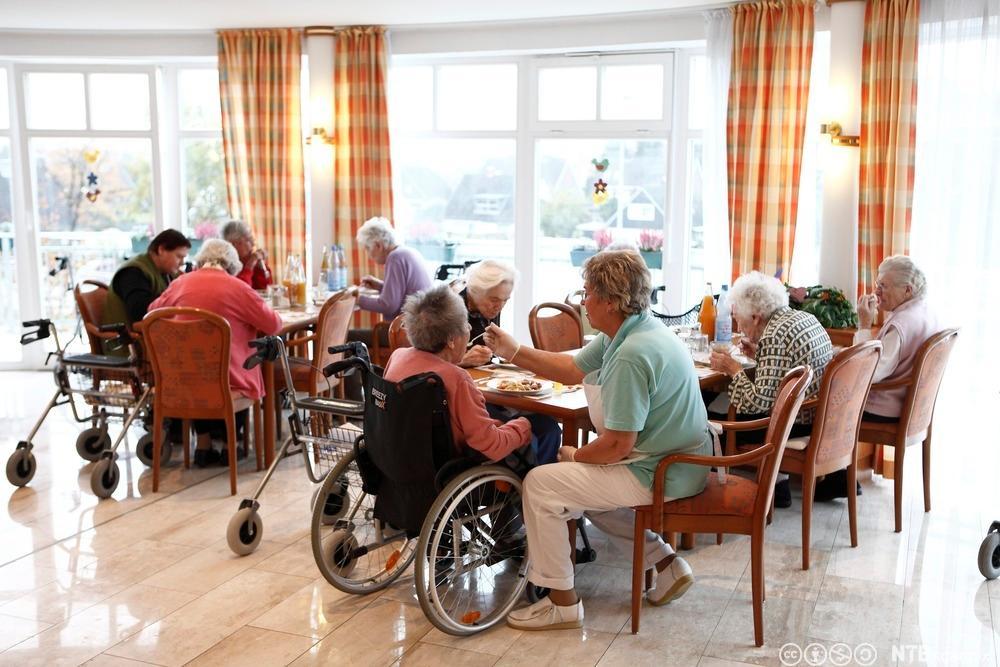 Måltid på en institusjon for eldre. Eldre mennesker sitter rundt et bord, noen i rullestol og noen med rullator. Foto.