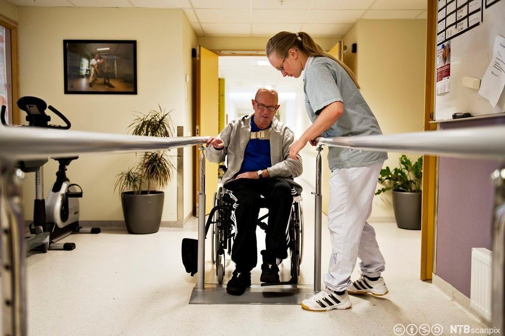 Helsefagarbeider hjelper slagrammet pasient med gåtrening. Foto.