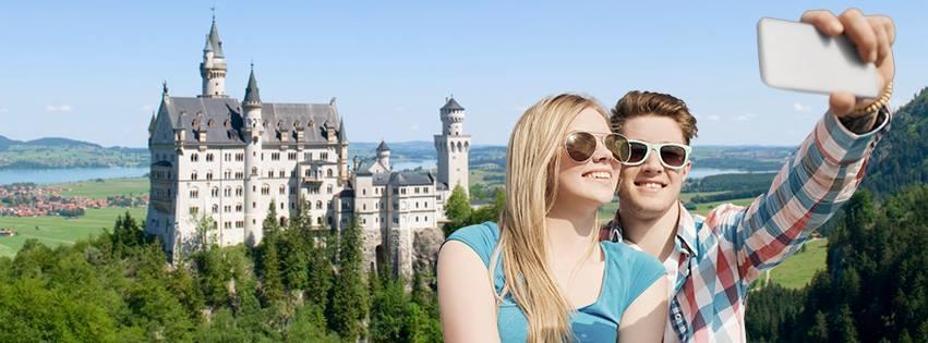 Bilde som viser to unge som tar en selfie. I bakgrunnen ser vi slott Neuschwanstein