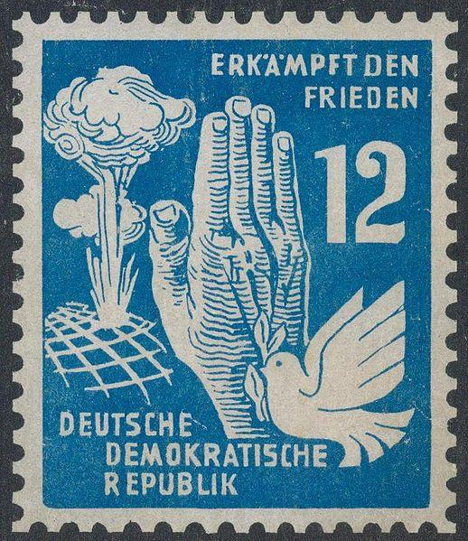 Tysk frimerke med ei atomsky, fredsdue og folda hender. Illustrasjon.