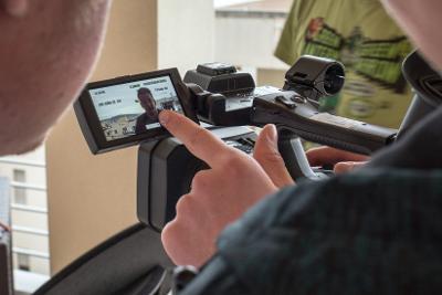 En person peker på skjermen til et kamera. To andre personer står på hver sin side av kameraet og er så vidt med på bildet. Foto.