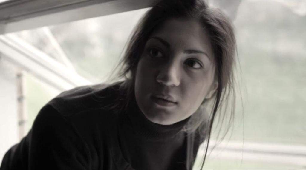 Mørkhåret jente kryper ut av vindu. Foto.
