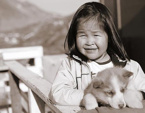 Inuittjente med en hund i hendene. Foto