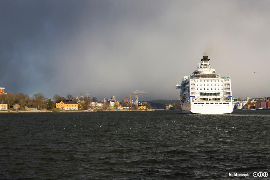 Et cruiseskip til sjøs med en havn i bakgrunnen. Foto.