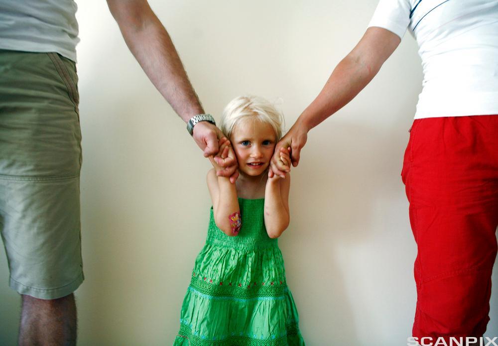 Liten jente holder sine foreldres hender. Foto.