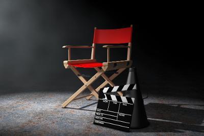 En klappstol i lyst tre med rødt trekk på sete og stolrygg står plassert midt i et ellers nesten tomt rom. Lyset faller inn fra venstre. På gulvet foran klappstolen står det en ropert og en filmklapper, det vil si ei krittavle som brukes til å notere opplysninger om sceneopptak til en film. Foto.