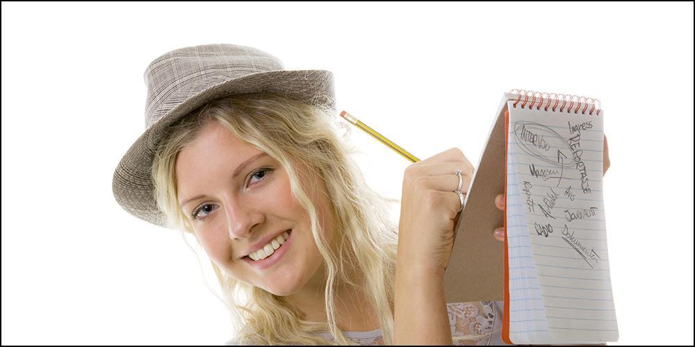 Jente som skriver på notatblokk. Foto.