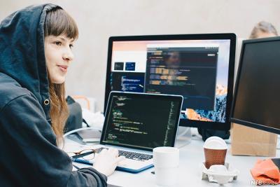 Ung kvinne sitter ved PC og programmerer. Foto.