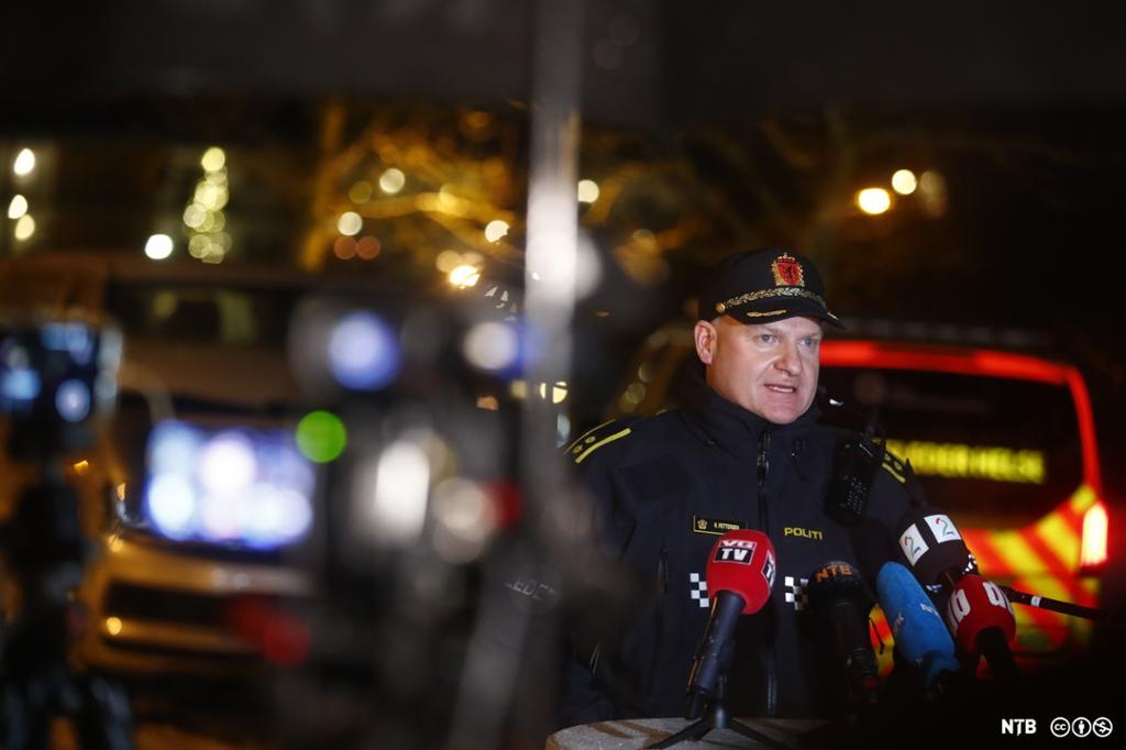 En mann i politiuniform står foran et bord med mikrofoner fra ulike norske medier. I bakgrunnen, som er ute av fokus, ser vi lys og utrykningskjøretøy. Foto.