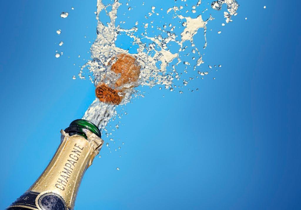 Korken spretter på en flaske champagne. Foto.