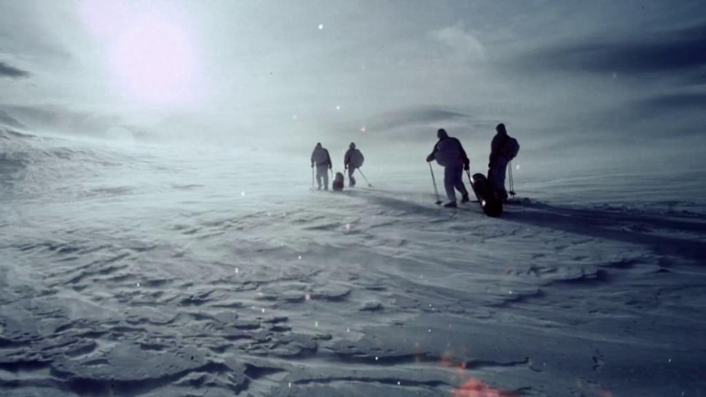 Fire personer i et øde og hvitt snølandskap.
