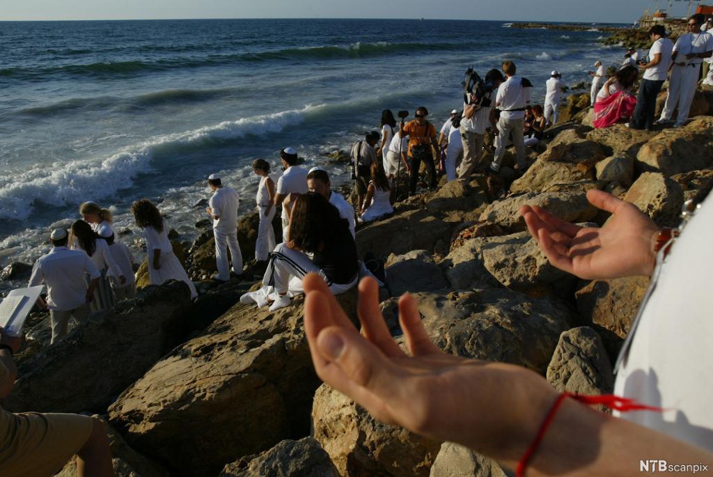 Mennesker kledd i hvitt står og sitter ved havet. Foto.