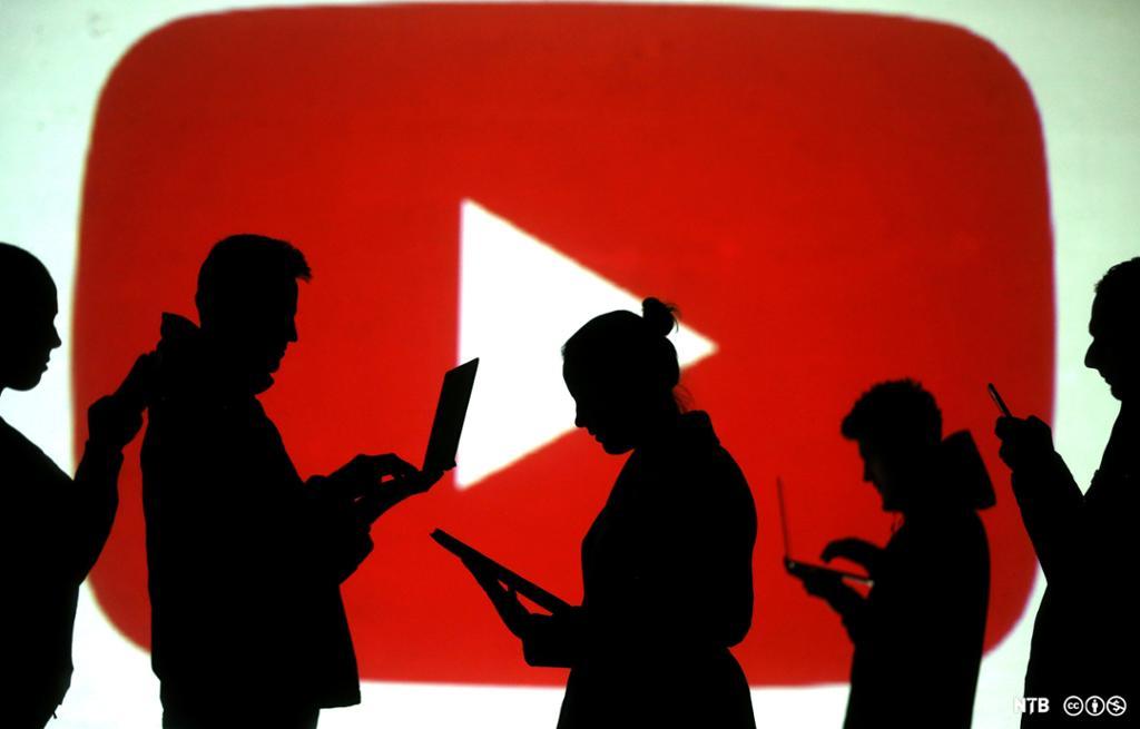 Foran YouTubes logo, en hvit play-knapp på rød bakgrunn, står silhuetter av fem personer med blikket festet i bærbare PC-er, nettbrett og mobiltelefoner. Illustrasjon.