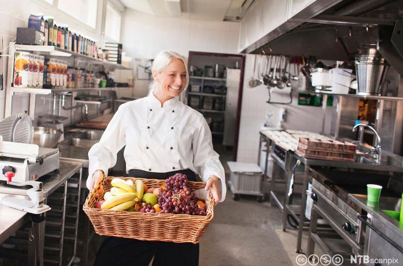 Kokk som bærer fruktkurv. Foto