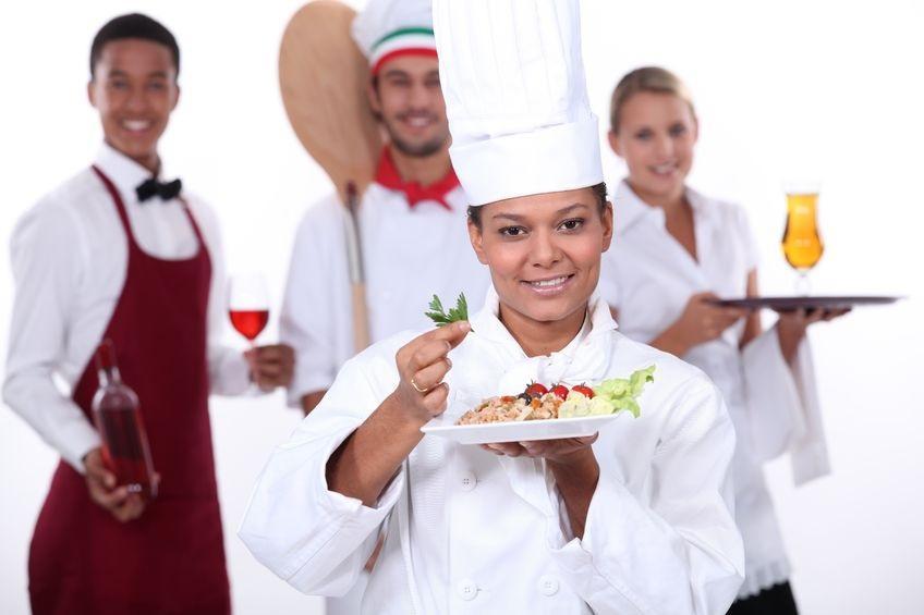 En kokk, to servitører og en baker poserer. Foto.