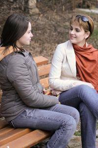 to jenter som sitter å snakker sammen på en benk. Foto.