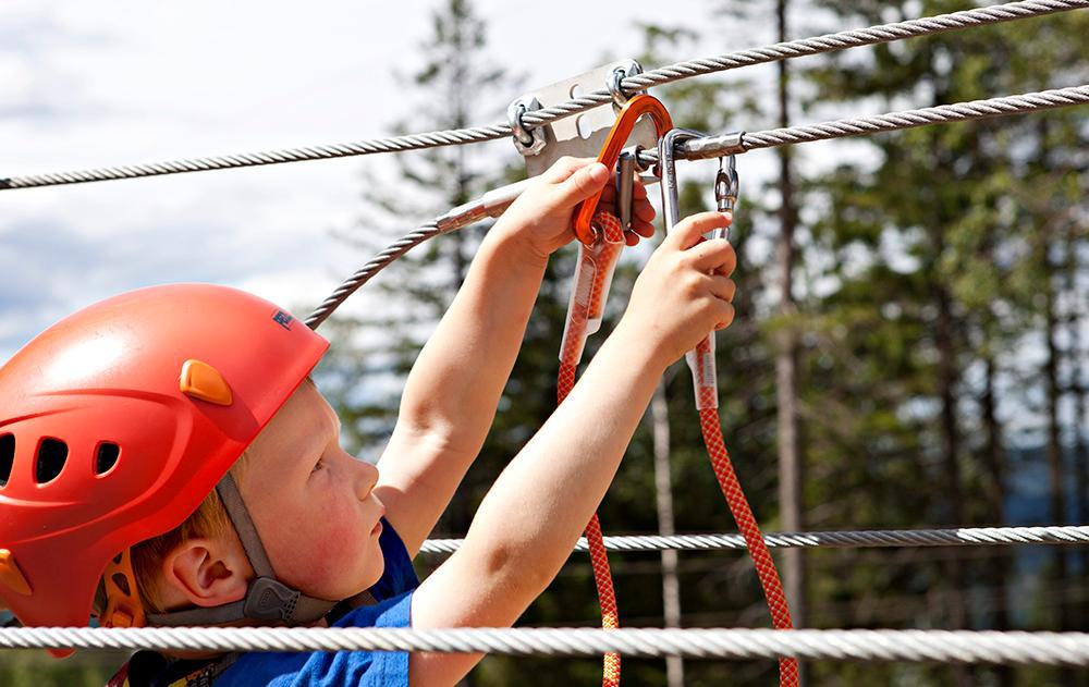 Et barn klatrer og har sikkerhetsutstyr. Foto.