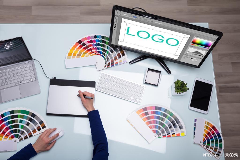 Designer i arbeid på datamaskin. Foto.