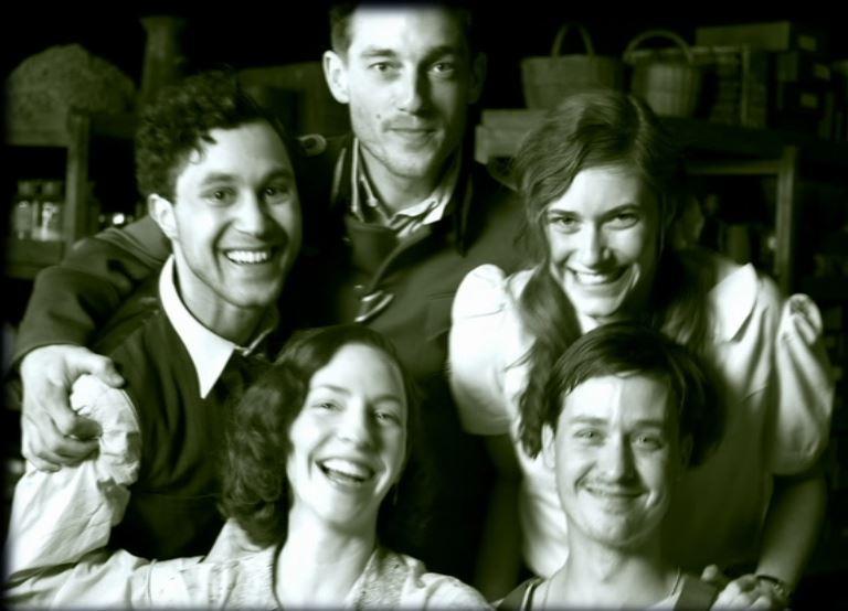 To kvinner og tre menn poserer. Foto i svarthvitt.