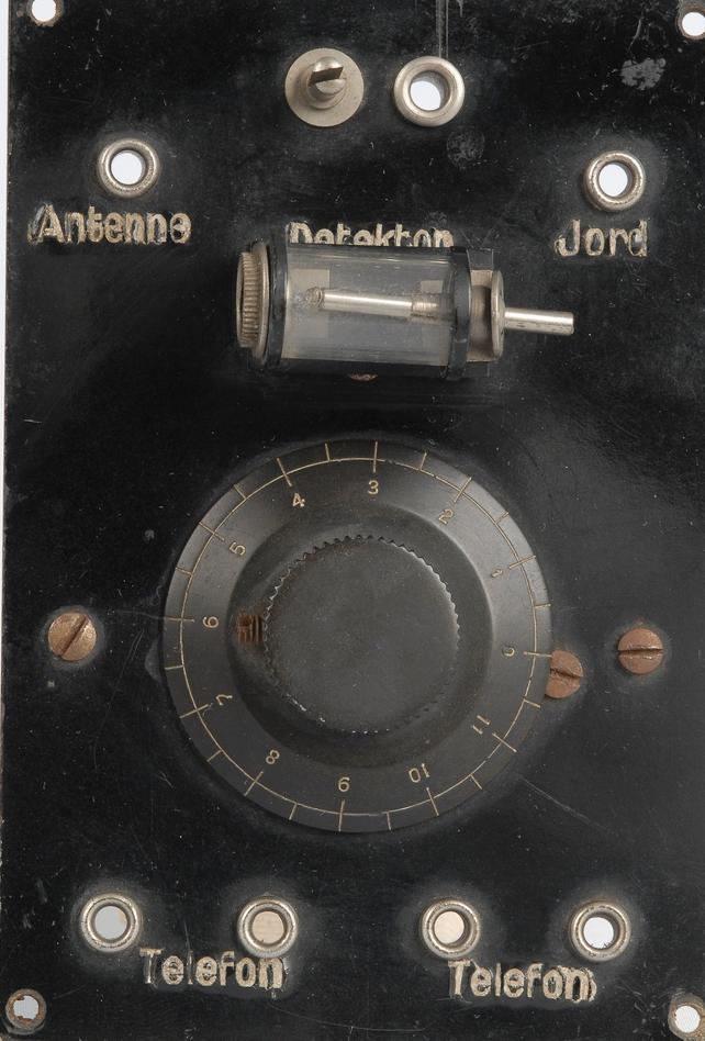 Fronten på et gammelt og litt rustent krystallapparat. Det er en svart boks med en dreieskive midt på og flere kontakter merket «Telefon», «Antenne», «Detektor» og «Jord». Foto.