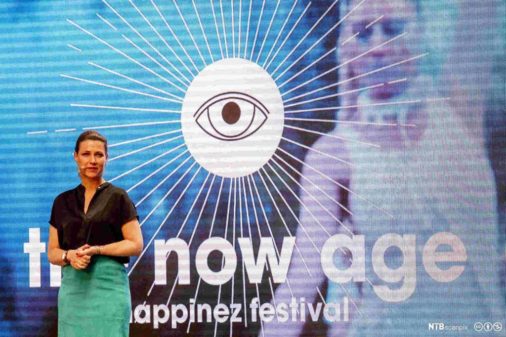 """Prinsesse Märtha Louise med mikrofon. Står foran en stor skjerm med bilde av et øye med linjer som stråler ut. Under øyet står det skrevet """"The Now Age. The Happinez Festival"""". Foto."""
