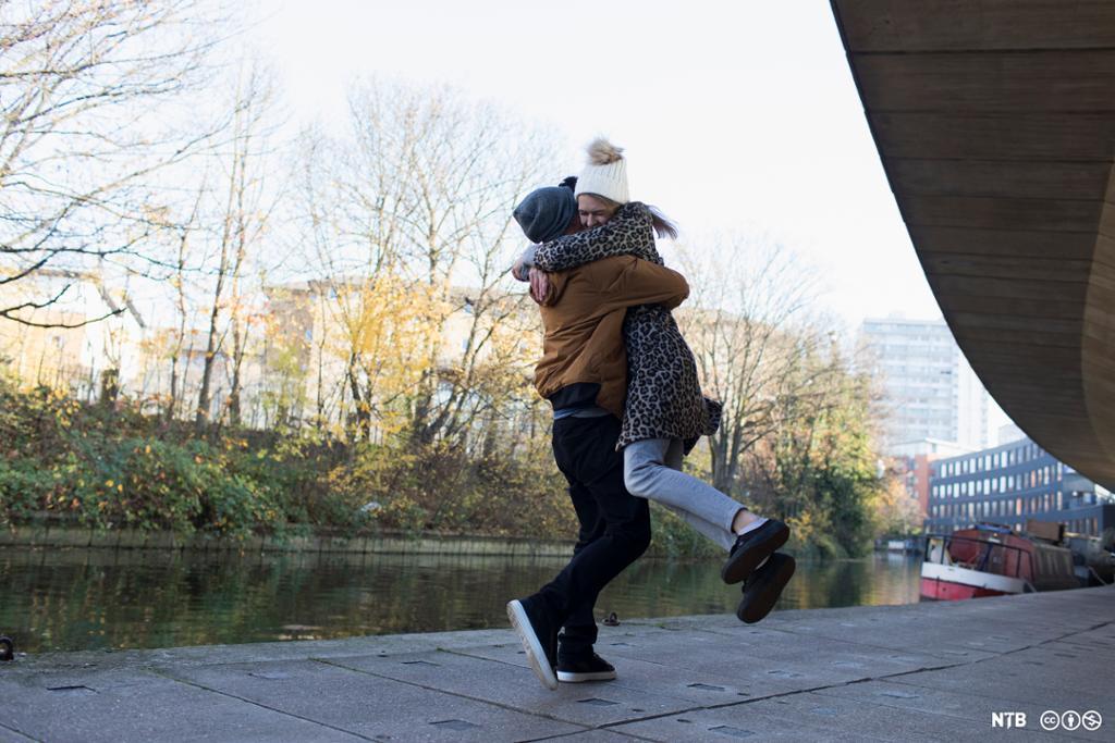 En gutt og en jente klemmer hverandre ved en kanal i en by. Gutten løfter jenta og svinger henne rundt. Det er høstfarger på trærne og gutten og jenta har tykke jakker og lue. Foto.