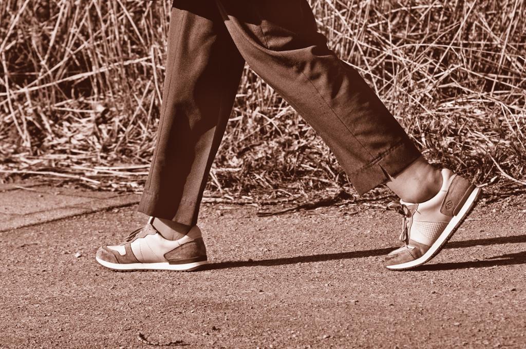 Føtter som spaserer på grus. foto.