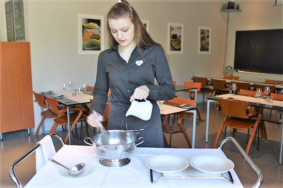 Servitør legerer suppe ved gjestens bord. Foto.