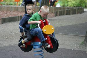 bildet viser to barn som sitter på en gyngehest sammen