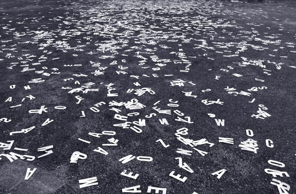 Hvite bokstaver ligger strødd på bakken. Foto.